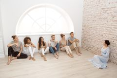 Group therapy session for couples. With trust issues. Talk out your problem. Young married couples happy talking while sitting on the therapy session with stock image