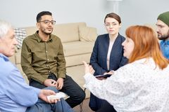 Group Therapy Session at Full Speed. Profile view of red-haired obese women discussing faced problem with other patients while participating in group therapy royalty free stock image