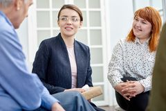 Group Therapy Session at Full Speed. Profile view of senior patient opening up to highly professional psychiatrist during group therapy session at cozy office stock images
