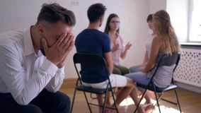 Group therapy session, sad man covers his face with hands on background of people sitting on chairs in circle stock video footage