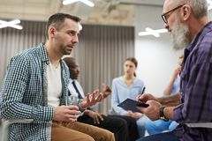 Group Therapy Session. Side view portrait of two mature men sharing problems with psychologist during group therapy session, copy space stock images