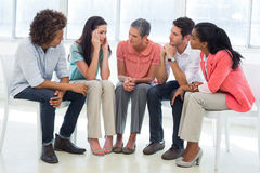 Group therapy in session sitting in a circle. In a bright room Stock Image