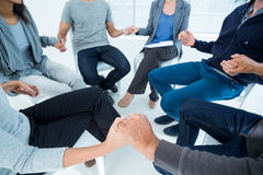 Group therapy in session sitting in a circle. In a bright room Stock Photo