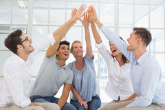 Group therapy in session sitting in a circle high fiving Royalty Free Stock Photos