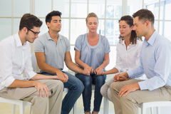 Group therapy in session sitting in a circle holding hands. In a bright room Stock Photos