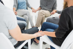 Group therapy in session sitting in a circle. With therapist Royalty Free Stock Photo