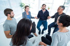 Group therapy in session sitting in a circle. With therapist royalty free stock image