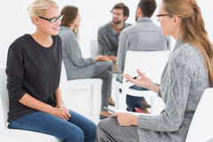 Group therapy session with therapist and client in foreground. Group therapy session in circle with therapist and client in foreground Royalty Free Stock Photography