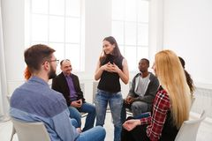 Therapist talking with a group at therapy session. Group therapy. Therapist talking with a rehab group at psychology support meeting stock photography