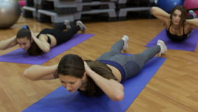 Group of three athletic women shakes the press lying on their stomach. stock video