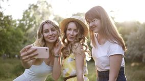 Group of three beautiful girls friends making picnic outdoor. They take selfie photo from smartphone. Sun shines on the stock video footage