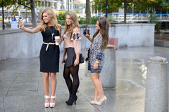Group of three beautiful young women take a selfie. Three young women (business women or students) pause in a city park to take a selfie photo with one cell Royalty Free Stock Photography