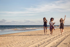 Group of three beautiful young women walking on the beach. Group of three beautiful young women running on the beach on a sunny day royalty free stock photo