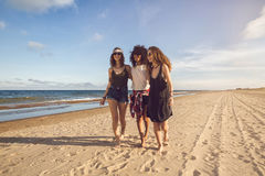 Group of three beautiful young women walking on the beach. On a sunny day royalty free stock image