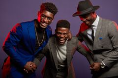 A group of three black men in stylish suits posing  in studio. Studio shot of group of African male young adult friends wearing smart suits having fun and stock photo