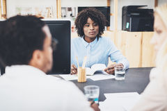 Group of three coworkers make great discussing about business plans in modern office. Young people working together. Horizontal, b Royalty Free Stock Photos