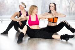 Group of three females doing dynamic fitness exercises in class stock images