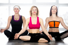 Group of three females meditating in class Royalty Free Stock Image