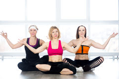 Group of three females practice yoga in class Royalty Free Stock Photography