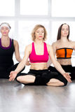 Group of three females sitting cross-legged in meditation in cla Royalty Free Stock Photo