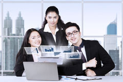 Group of three financial consultants. Group of three young financial consultants looks successful and smiling at the camera with virtual chart on the laptop in Stock Images