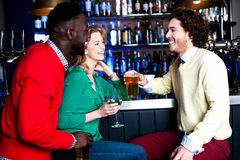 Group of three friends in a bar drinking beer Royalty Free Stock Photos