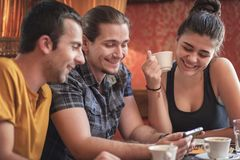 Group of three friends in a coffee shop. Group of friends in a coffee shop, discussing some content on their phone Stock Image