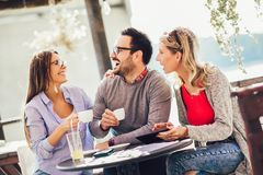 Group of three friends having fun a coffee together. Two women and men at cafe talking laughing and using digital tablet stock image