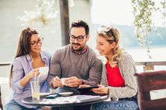 Group of three friends having fun a coffee together. Two women and men at cafe talking laughing and using digital tablet royalty free stock photo
