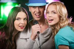 Group of three friends singing with microphone. Stock Photo