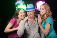 Group of three friends singing with microphone. Man and two women standing on black background and singing Stock Photos