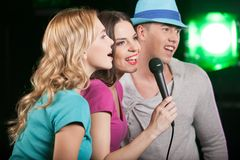 Group of three friends singing with microphone. Profile of men and women standing on black background and singing Stock Photos