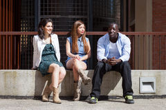 Group of three friends. Talking together outdoors on a bench Stock Images