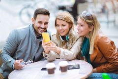 Group of three friends using phone in outdoor cafe Stock Photo