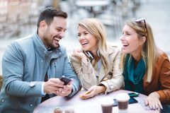 Group of three friends using phone in outdoor cafe Royalty Free Stock Photo