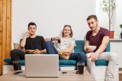 Group of three friends watching something on laptop. Friendship and quality time Royalty Free Stock Photo