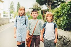 Group of three funny kids wearing backpacks walking back to school. Cute kids with backpacks walking back to school Royalty Free Stock Images