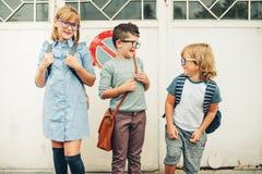 Group of three funny kids wearing backpacks walking back to school. Girl and boys wearing eyeglasses posing outdoors stock photo