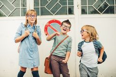 Group of three funny kids wearing backpacks walking back to school Stock Photo