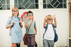Group of three funny kids wearing backpacks walking back to school stock photos