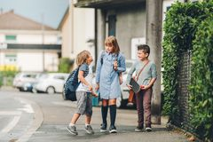 Group of three funny kids wearing backpacks walking back to school Stock Photography