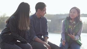 Group of three happy Asian teenagers sitting on the street at sunset time. stock footage