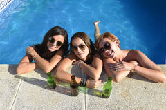 Group of three happy beautiful girl friends having bath in swimm. Group of three happy and beautiful young girl friends having bath in swimming pool together Stock Photo