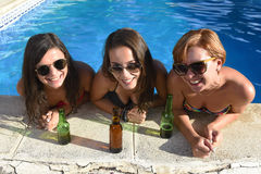 Group of three happy beautiful girl friends having bath in swimm. Group of three happy and beautiful young girl friends having bath in swimming pool together Royalty Free Stock Photography