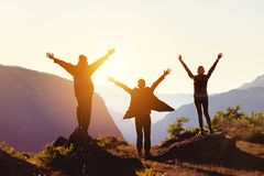 Travel concept with three happy friends against sunset mountains. Group of three happy friends greetings sunset sun with raised hands against mountains. Travel Royalty Free Stock Photos