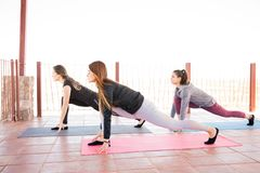 Group of women in low lunge yoga pose. Group of three hispanic women doing low lunge pose at yoga class stock photos