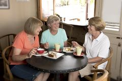 Group of three lovely middle age senior mature women girlfriends meeting for coffee and tea with cakes at coffee shop sharing time Royalty Free Stock Photo