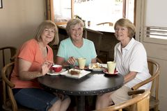 Group of three lovely middle age senior mature women girlfriends meeting for coffee and tea with cakes at coffee shop sharing time. Together enjoying Stock Image