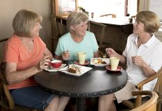 Group of three lovely middle age senior mature women girlfriends meeting for coffee and tea with cakes at coffee shop sharing time Royalty Free Stock Images