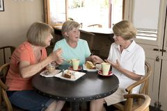 Group of three lovely middle age senior mature women girlfriends meeting for coffee and tea with cakes at coffee shop sharing time. Together enjoying Royalty Free Stock Image